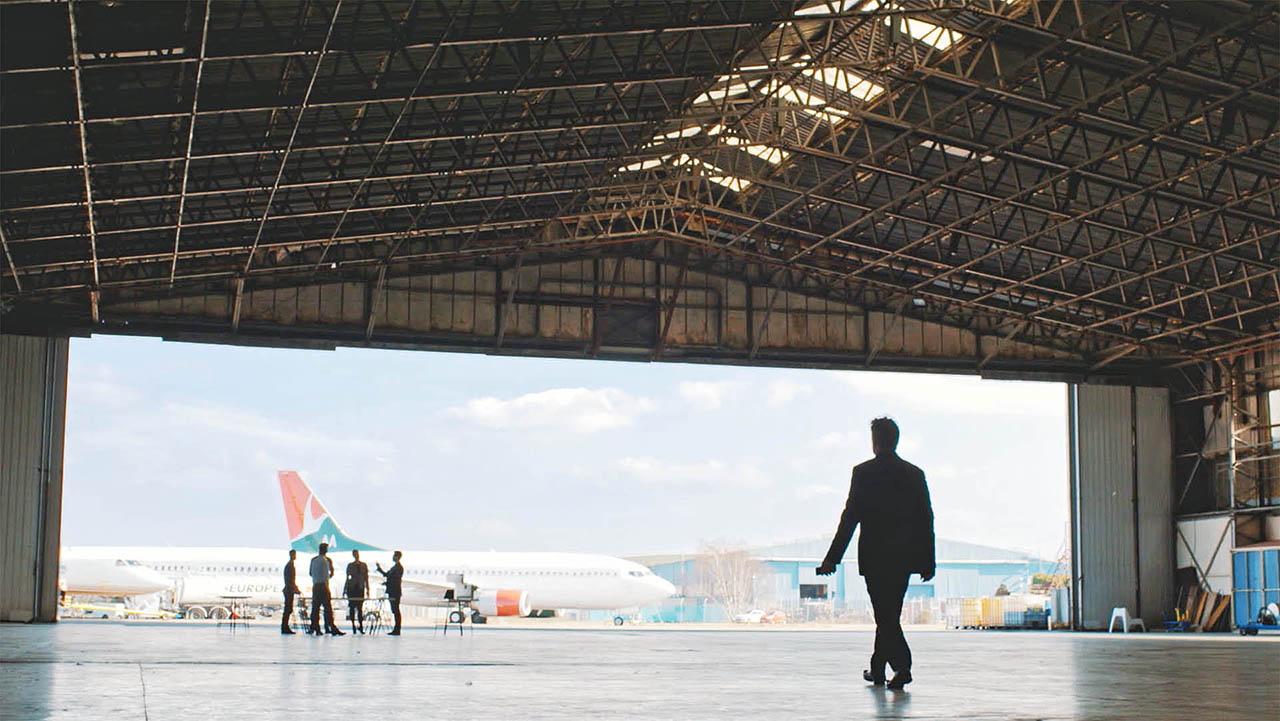 Aim Altitude Corporate Videos - Man walking through Aeroplane Hanger